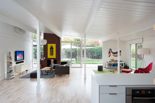 Built in the early 1970s, the house's kitchen, living, and dining areas were originally divided into three distinct zones. In order for this great room to flow as one, Klopf Architecture removed the glass doors and solid walls separating the enclosed atrium from the kitchen and living room.  A Herman Miller trade poster, Design Within Reach book tower, and IKEA sofa mingle in the space.