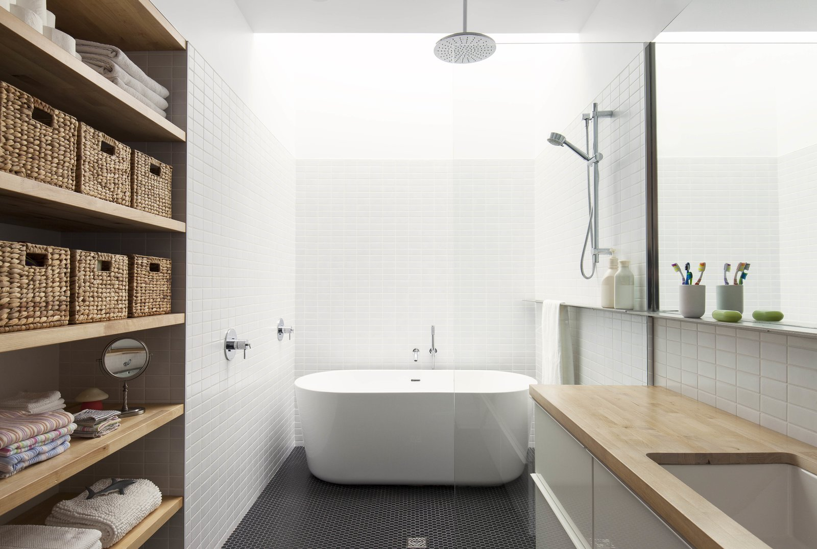 In the renovated bathroom, a freestanding bathtub sits beneath a skylight that runs the width of the room. A large mirror hangs above the vanity, which is outfitted with a butcher-block countertop. Black mosaic tiles were used on the floor.  Photo 12 of 15 in A Transformative Duplex Renovation in Montreal