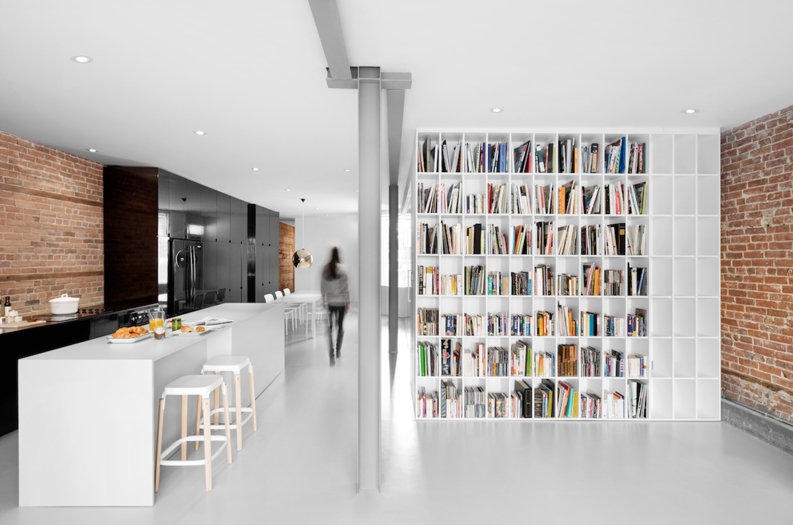 Kitchen and White Cabinet The steel beam original to the building was left exposed but toned down with gray, flame-proof paint. It runs the length of the flat, delimiting the passage area.  Best Photos from A Futuristic Apartment with a Glass-Enclosed Bedroom