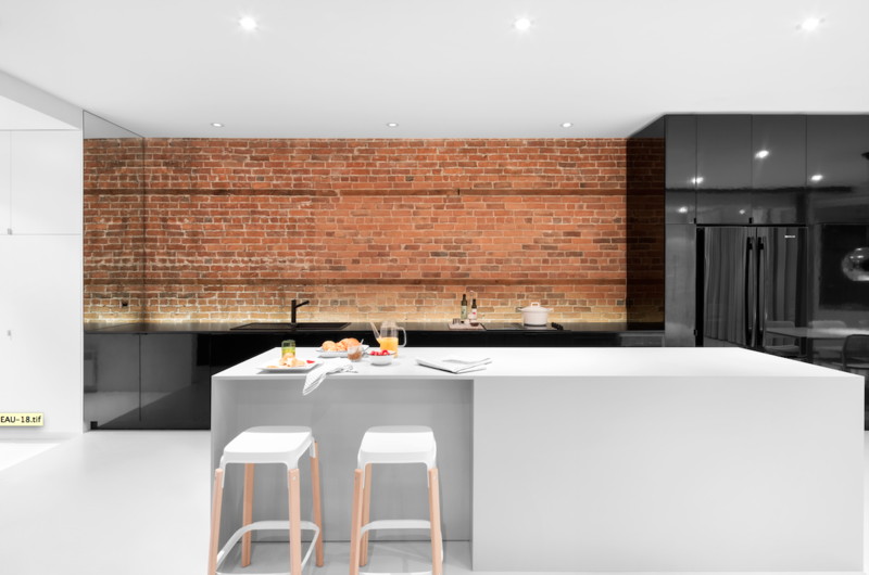 An illuminated brick wall makes a nice backdrop for glossy black cabinets and Jenn-Air appliances. When guests come over for dinner, they can sit on stools by Ronan & Erwan Bouroullec and chat with the cook over a custom island that matches the floor. The fixtures are by Blanco.