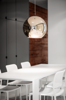 """Goneau matched Audrey Chairs from Kartell with a dining table she designed herself. """"It becomes the visual continuity of the kitchen island, by its dimensions and material,"""" she says. A bronze copper pendant by Tom Dixon hangs above it."""