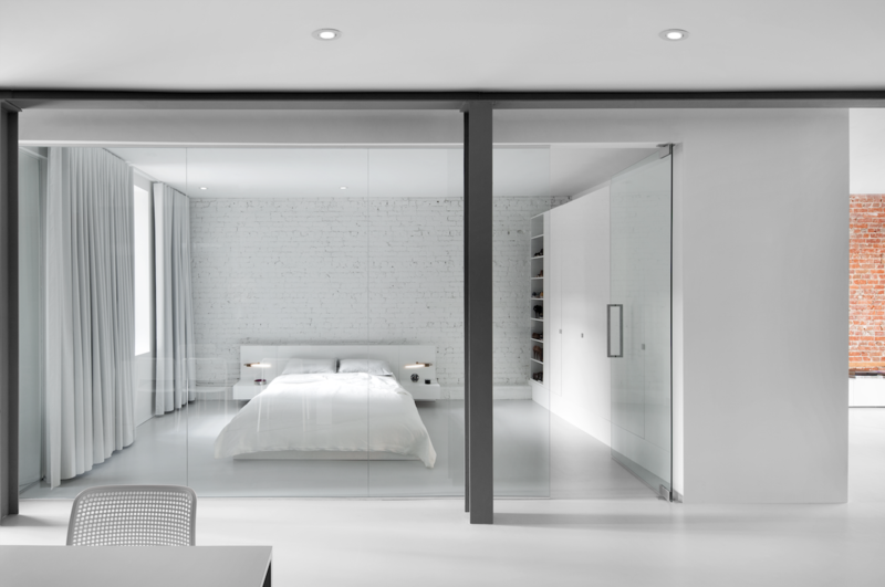 The bedroom is enclosed with a glass wall. A blackout curtain can be drawn closed for privacy. An Ikea cabinet and custom white lacquered shelves provide plenty of closet space.