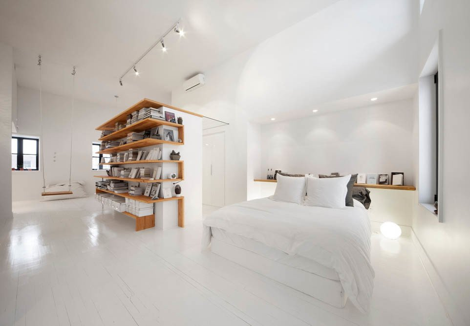Bedroom, Lamps, Painted Wood, Recessed, Shelves, Track, Floor, and Bed The architecture firm L. McComber Itée demolished a sloping ceiling in this Montreal attic to create a bright, roomy live-work space.  Best Bedroom Painted Wood Bed Photos from A Transformative Attic Renovation in Montreal