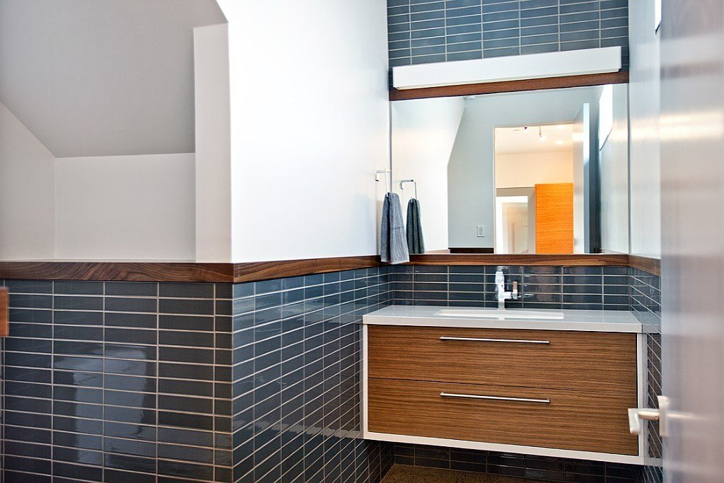 In the powder room, the vanity surface is Silestone, the sink is Kohler, and the faucet is Brizo. The drawer pulls are from Siro designs. An instant hot water system from Eemax was installed.  A Modern, Energy-Efficient Smart Home by Diana Budds