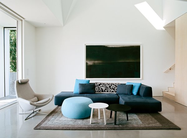 White walls and concrete floors define the ground level, where a Bend sectional and Metropolitan chair by B&B Italia, an Arper pouf, Bella coffee tables by HAY, and a Peace Industry rug furnish the main living area.