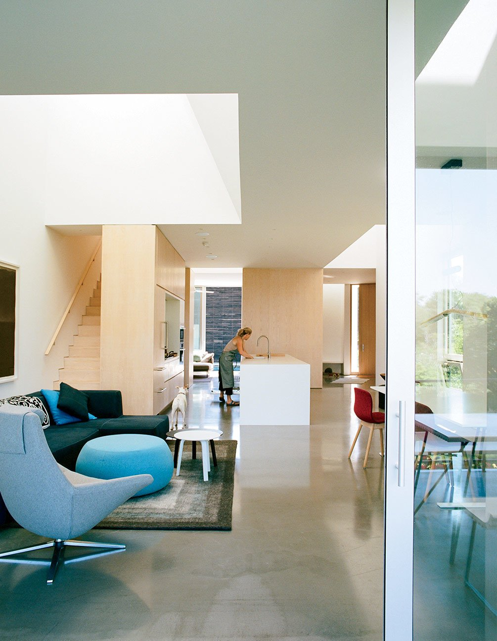 Living Room, Sofa, Chair, Ottomans, Coffee Tables, and Concrete Floor The kitchen contains an island countertop made of Corian in Glacier White.  Photo 8 of 16 in An Idyllic Rhode Island Summer Cottage Is the Perfect Escape for a New York Family