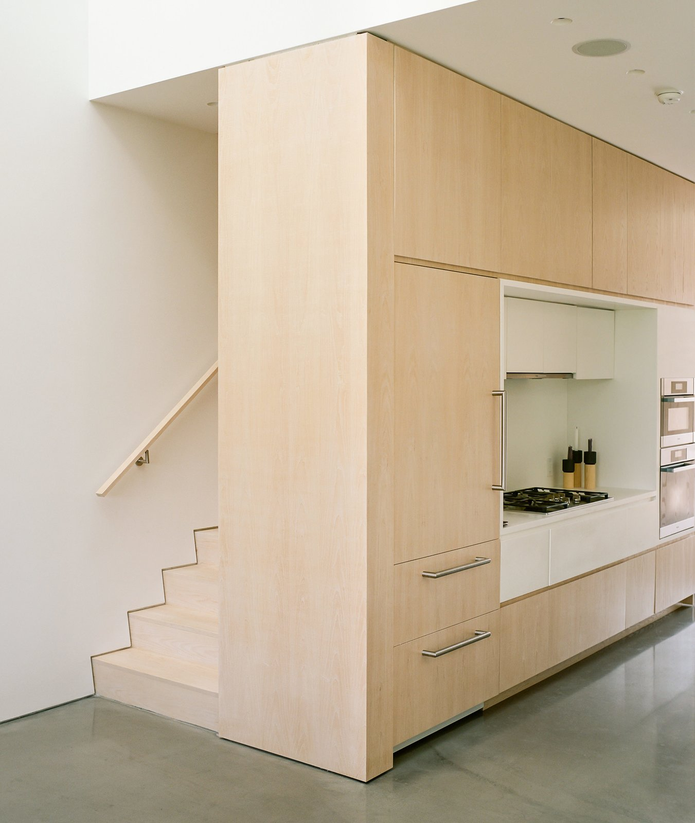 """Kitchen, Range, Wood Cabinet, Recessed Lighting, and Ceiling Lighting Light streams from above into the living room and kithen thanks to the home's largest skylight. This skylight isn't one large window but two: one on the eastern side of the double-height volume, and one on the western. In between them are sculptural, pyramid-shaped forms that block and diffuse the sunlight throughout the day. In the words of the architects, they """"add to the unexpective quality of light"""" in the space.  Photo 9 of 16 in An Idyllic Rhode Island Summer Cottage Is the Perfect Escape for a New York Family"""