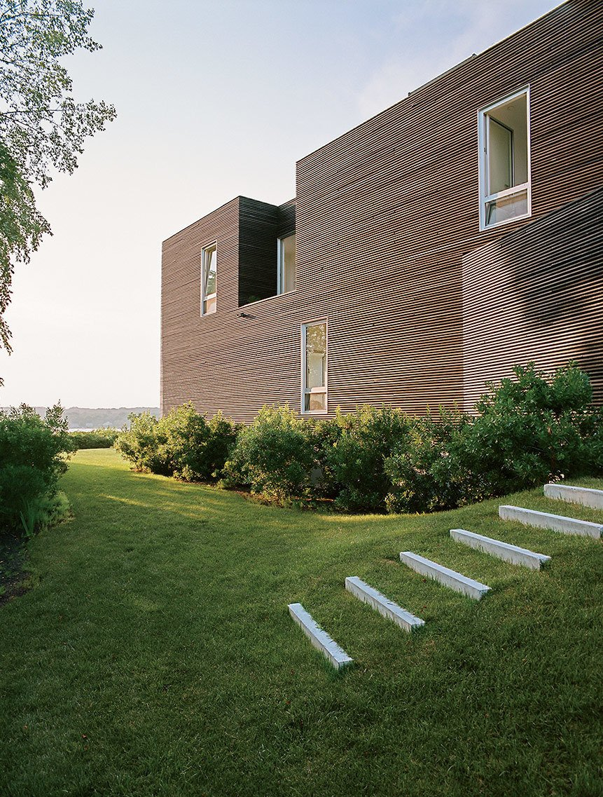 """Exterior, House Building Type, and Flat RoofLine The home is defined by two types of windows: large punch openings for views onto the landscape and vertical windows everywhere else.  Search """"charles birnbaum future landscape architecture"""" from An Idyllic Rhode Island Summer Cottage Is the Perfect Escape for a New York Family"""