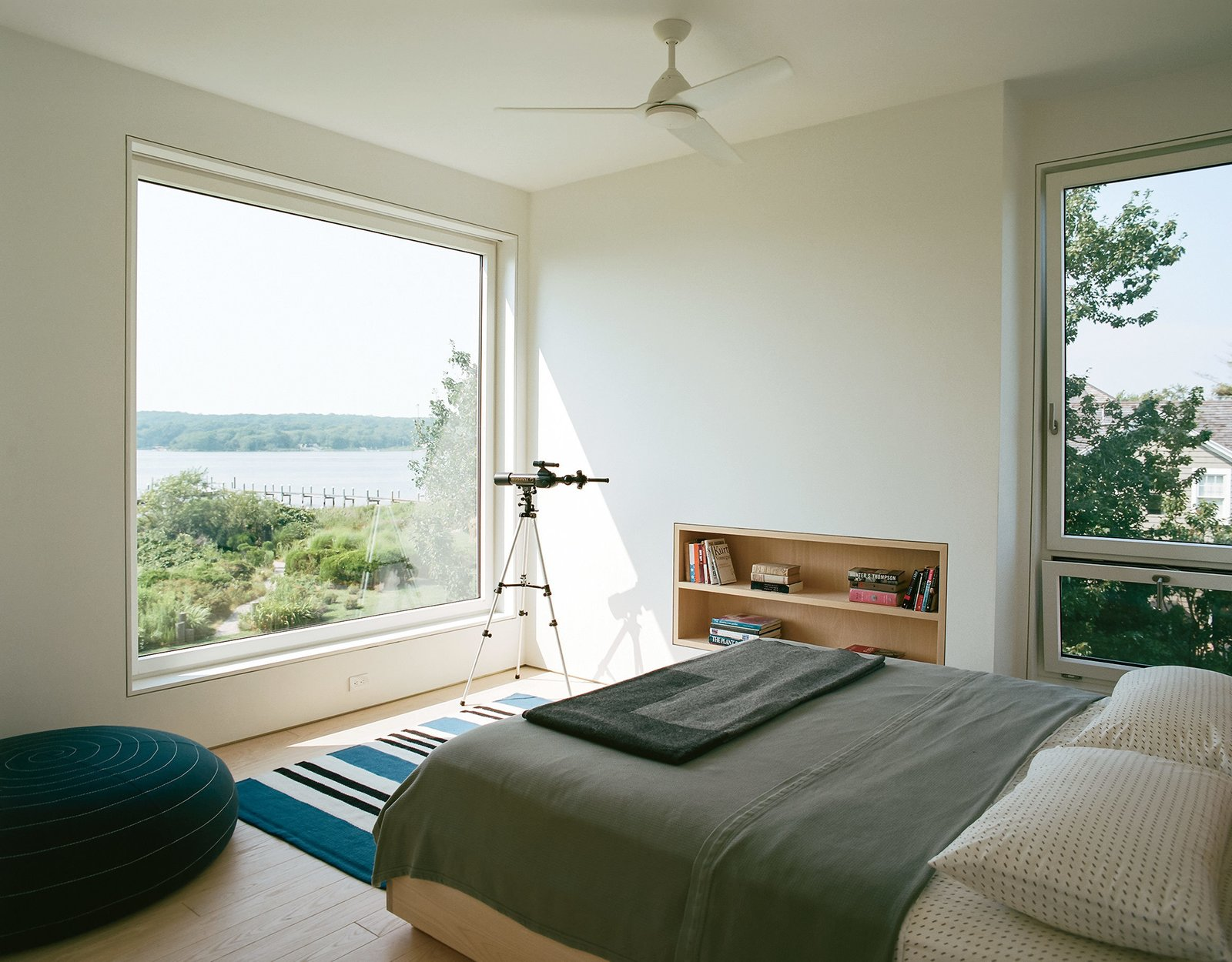 "Bedroom, Bed, and Shelves In the master bedroom, a custom ash frame takes advantage of the expansive view.  Search ""stockholm elevations architectural print maple frame"" from An Idyllic Rhode Island Summer Cottage Is the Perfect Escape for a New York Family"