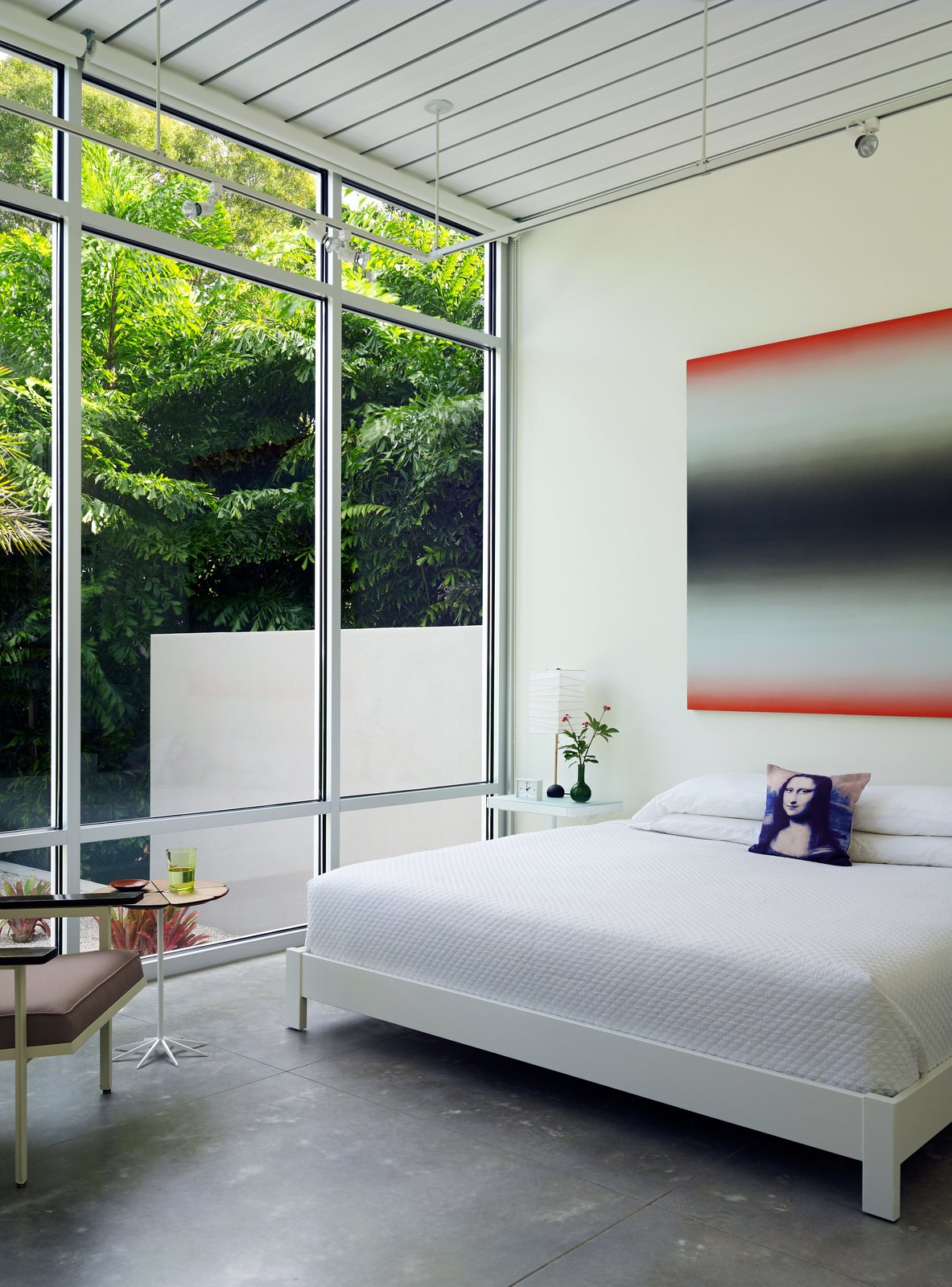 Bedroom, Bed, Chair, Night Stands, Track Lighting, and Concrete Floor In the master suite, a painting by Eric Freeman hangs over a West Elm bed.  Photos from This Sparkling New Home Is a Perfect Remake of Classic Sarasota School Modernism