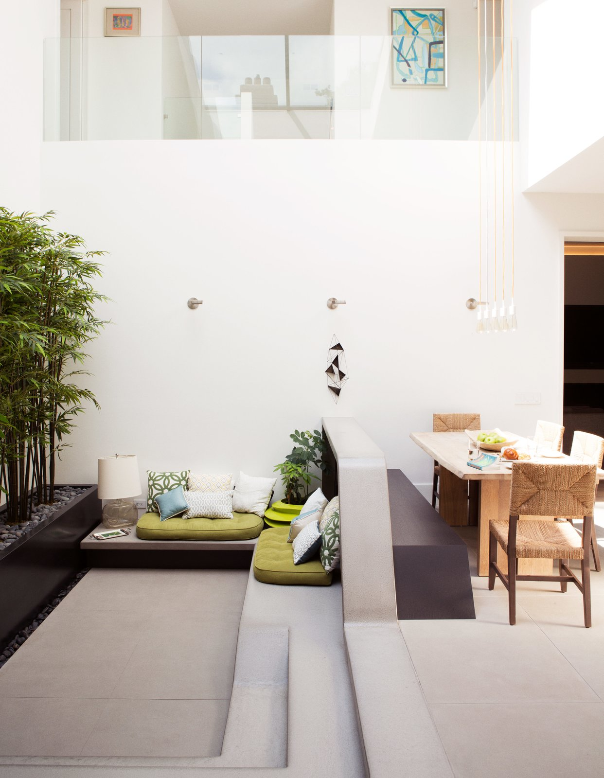 Living Room, Bench, and Concrete Floor Architect Kevin Toukoumidis and his team at dSPACE Studio reworked an unusual layout of a Chicago home to fit its new owners: a family with two children and a dog. The result was a radical change without dramatic intervention, particularly of the home's large central atrium space.  Photo 4 of 13 in An Impressive 20-Foot Skylight Transforms a Jumbled Chicago Home