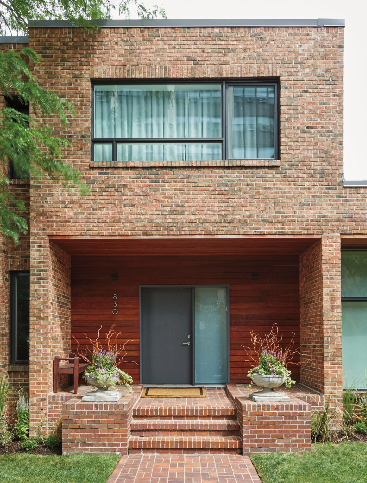 Exterior, Brick Siding Material, and Flat RoofLine Because the house is located in a historic area, the exterior updates were limited to new windows and ipe cladding around the front door.  Photo 2 of 13 in An Impressive 20-Foot Skylight Transforms a Jumbled Chicago Home