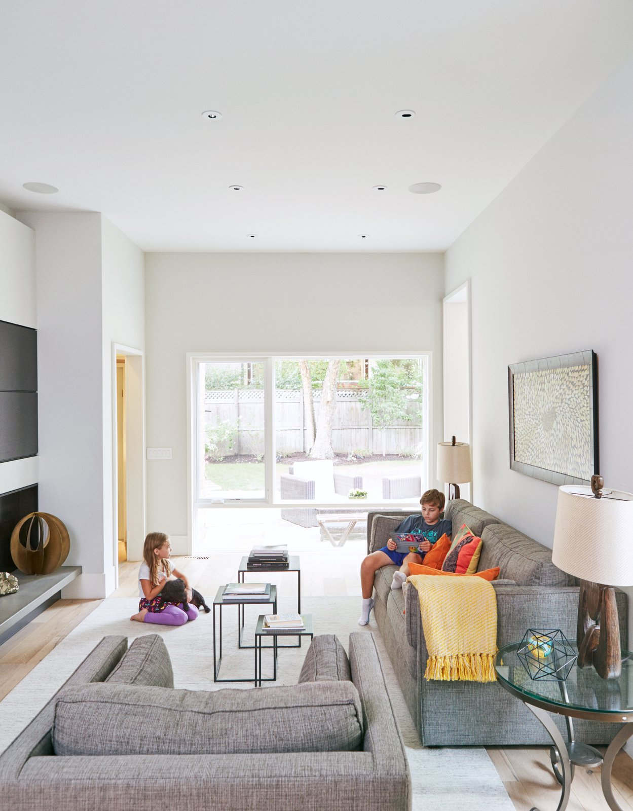 Living Room, Chair, Sofa, Ceiling Lighting, and Recessed Lighting To create privacy, the residents opted to keep the family room separate from the other living spaces. The sofa, chair, and rug are from Room & Board.  Photo 7 of 13 in An Impressive 20-Foot Skylight Transforms a Jumbled Chicago Home