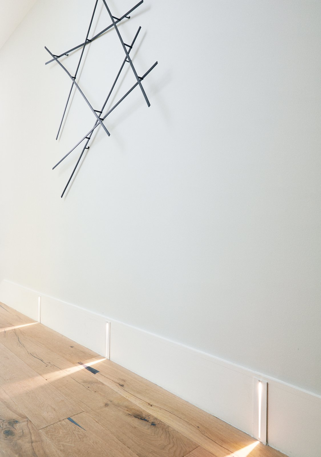 Hallway and Light Hardwood Floor Sistemalux's integrated LED Step lighting adds a dynamic touch to a passageway.  Photo 9 of 13 in An Impressive 20-Foot Skylight Transforms a Jumbled Chicago Home