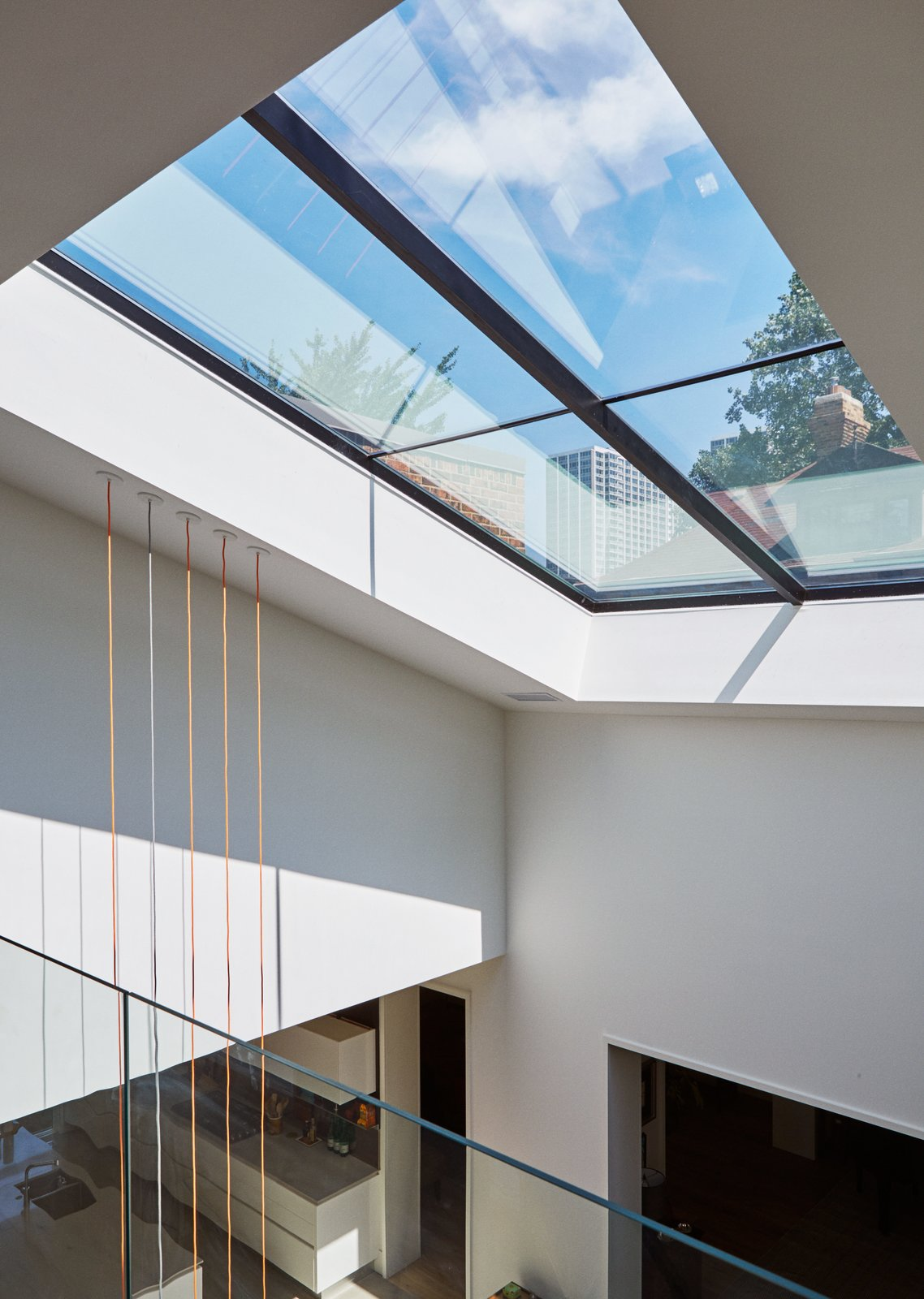 Hallway A newly expanded window over the atrium allows glimpses of the surrounding neighborhood.  Photo 11 of 13 in An Impressive 20-Foot Skylight Transforms a Jumbled Chicago Home