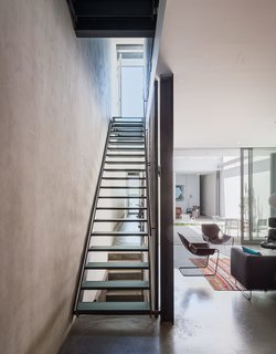 "Long, unobstructed corridors along the spine of the house provide ample cross-ventilation during warmer months—as well as sightlines that unite different areas of the home's narrow, linear footprint. ""When you're in the back of the building, you can literally see the front door of the person across the street,"" says architect and resident Philippe Baumann. Thick industrial glass lines the footing of the stairwell with subtle transparency, allowing light to also traverse the space vertically."