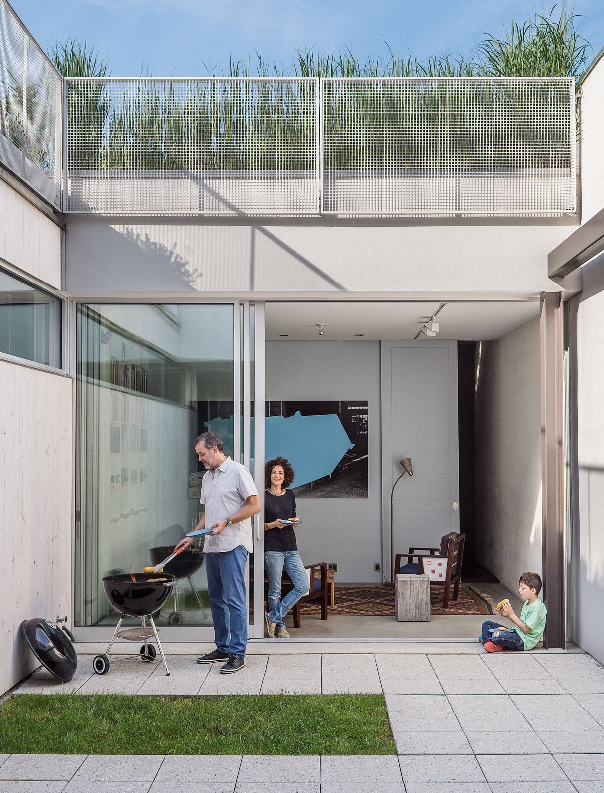 "Outdoor, Small, Concrete, Grass, and Back Yard The home's enclosed courtyard sits at ""the heart of the structure,"" says Baumann, who resides with his wife, Lisa Sardinas, and eight-year-old son, Oskar. ""This is clearly the dominant space; everything flexes towards it."" Baumann cast the square concrete floor tiles himself, enlisting the help of his son. A small, neat patch of grass—a playful nod to the archetypal domestic lawn—is edited down to a charming folly.  Best Outdoor Back Yard Grass Photos from A Rooftop Garden Completes This Urban Pastoral Home"