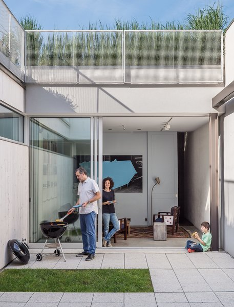 "The home's enclosed courtyard sits at ""the heart of the structure,"" says Baumann, who resides with his wife, Lisa Sardinas, and eight-year-old son, Oskar. ""This is clearly the dominant space; everything flexes towards it."" Baumann cast the square concrete floor tiles himself, enlisting the help of his son. A small, neat patch of grass—a playful nod to the archetypal domestic lawn—is edited down to a charming folly."