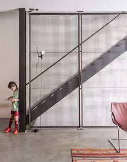 The sculpture on the wall is by artist Peter Dudek, a friend of the family, and the pendants are by Glashütte Limburg. Baumann made a point to integrate industrial materials throughout, exposing steel beams and setting the floor in concrete.