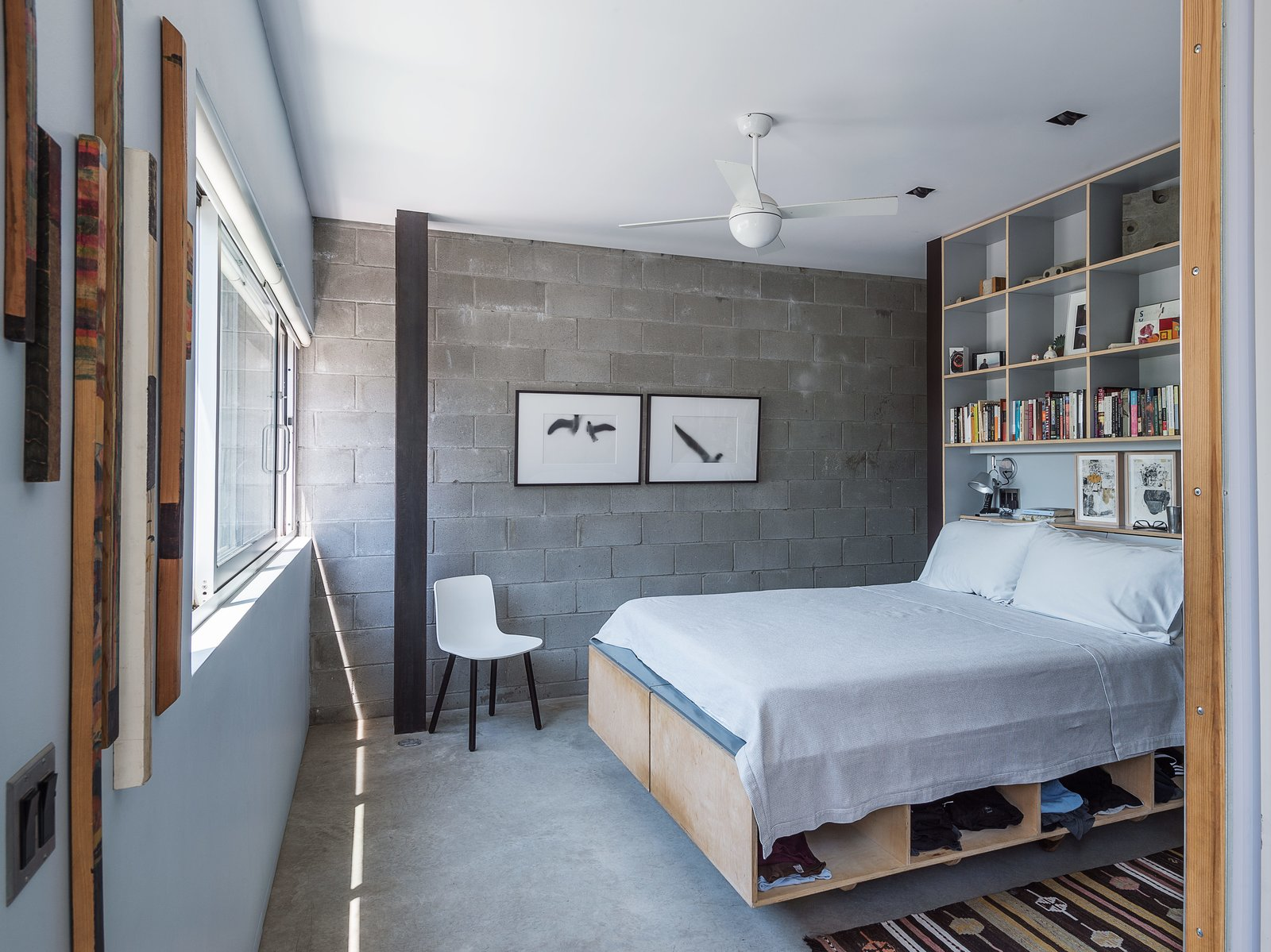 Bedroom, Bed, Chair, Ceiling Lighting, and Concrete Floor Baumann designed the plywood bed frame and shelving unit in the master bedroom, adjacent to an exposed cinder-block wall, a new addition to the structure.   Bedroom