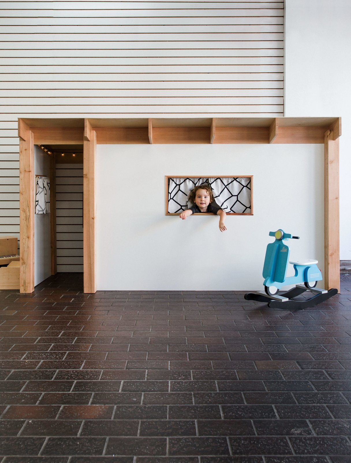 """Kids Room and Playroom Room Type Children streaming in for a workshop are greeted by an Eichler-inspired playhouse (dubbed the """"Tikeler"""") designed and built by The Butterfly Joint's founder, Danny Montoya.  Photo 1 of 1 in In a San Francisco Workshop, Kids Take on Carpentry with Mini Chisels and Saws"""