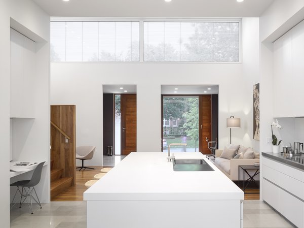 """According to Paul Raff, the biggest design challenge was creating a functional home that would accommodate the family's regular activities (dining, music, play, homework) all on one level. This was solved by """"collaging spaces of different shapes and sizes together, and by interconnecting them all with a very open and seamlessly integrated kitchen."""" The airy family kitchen features Loire limestone floors, BassamFellows Tractor stools, and an Eames molded plastic chair."""