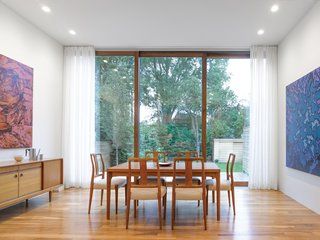 The leafy backyard is the backdrop for the family's dining room. Walnut hardwood flooring adorns the space, along with a vintage Danish modern dining set and sideboard.