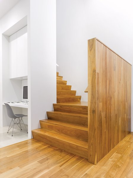 """We composed the house to have its highest, brightest space in the middle,"" says Paul Raff. Warm wood stairs lead to the second floor, which houses guest bedrooms, bath, and a kitchenette for the family's frequent visitors."