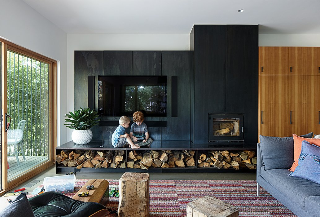 "Living Room, Sofa, Wood Burning Fireplace, Standard Layout Fireplace, End Tables, Recessed Lighting, and Chair Hufft Projects designed the blackened steel ""fireplace wall,"" which includes a Lennox wood-burning stove and an entertainment center. The Vela sofa is by Room & Board, and the rug is composed of carpet tiles from FLOR.  97+ Modern Fireplace Ideas from This Kansas City Home Looks Like Its Neighbors, But Reveals a Truly Modern Sensibility"