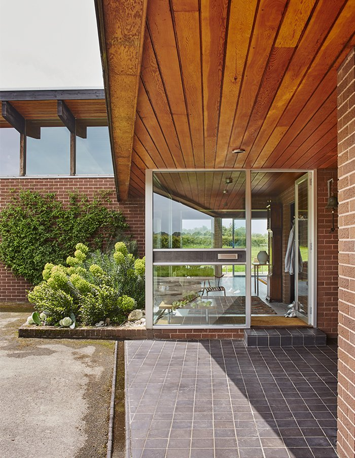 """Outdoor, Small Patio, Porch, Deck, and Tile Patio, Porch, Deck The house is located on a 25-acre site. It sat unsold on the property for two years before the couple discovered it.  Search """"glass house australia's sunshine coast"""" from Quirky 1970s House in the English Countryside Showcases an Amazing Modern Furniture Collection"""
