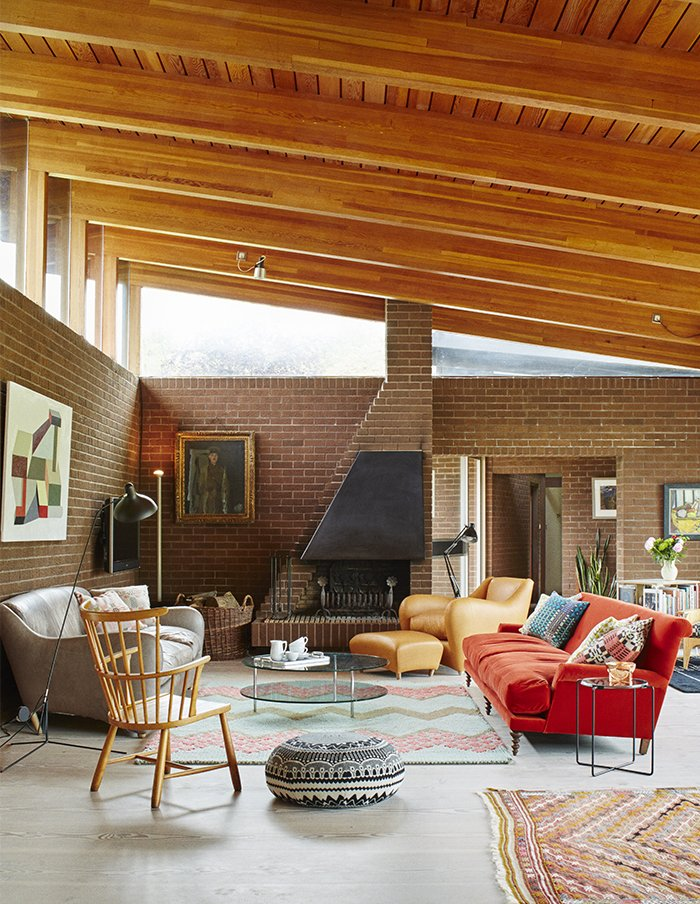 Living Room, Standard Layout Fireplace, Wood Burning Fireplace, Sofa, Coffee Tables, Rug Floor, and Chair In the open-plan living and dining room, a dramatically sloped roofline allows for generous clerestory windows.  Furniture from Quirky 1970s House in the English Countryside Showcases an Amazing Modern Furniture Collection