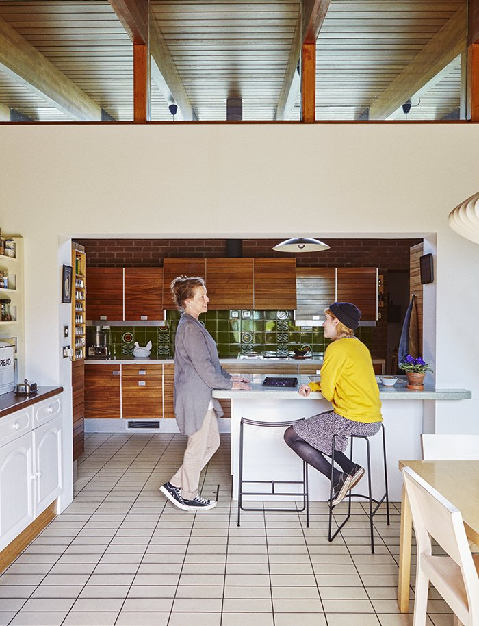 Kitchen, White Cabinet, and Wood Cabinet Louise Jenkins, left, chats with her daughter, Freya, who sits on a powder-coated Slatted bar stool by Jasper Morrison manufactured in Lancashire.  Photo 5 of 18 in Quirky 1970s House in the English Countryside Showcases an Amazing Modern Furniture Collection