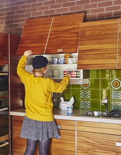 """""""The kitchen is pretty astonishing, really, considering it's 40 years old,"""" says resident Louise Jenkins. Large square tiles in green with sunflowers compliment the cabinets' natural wood finish."""