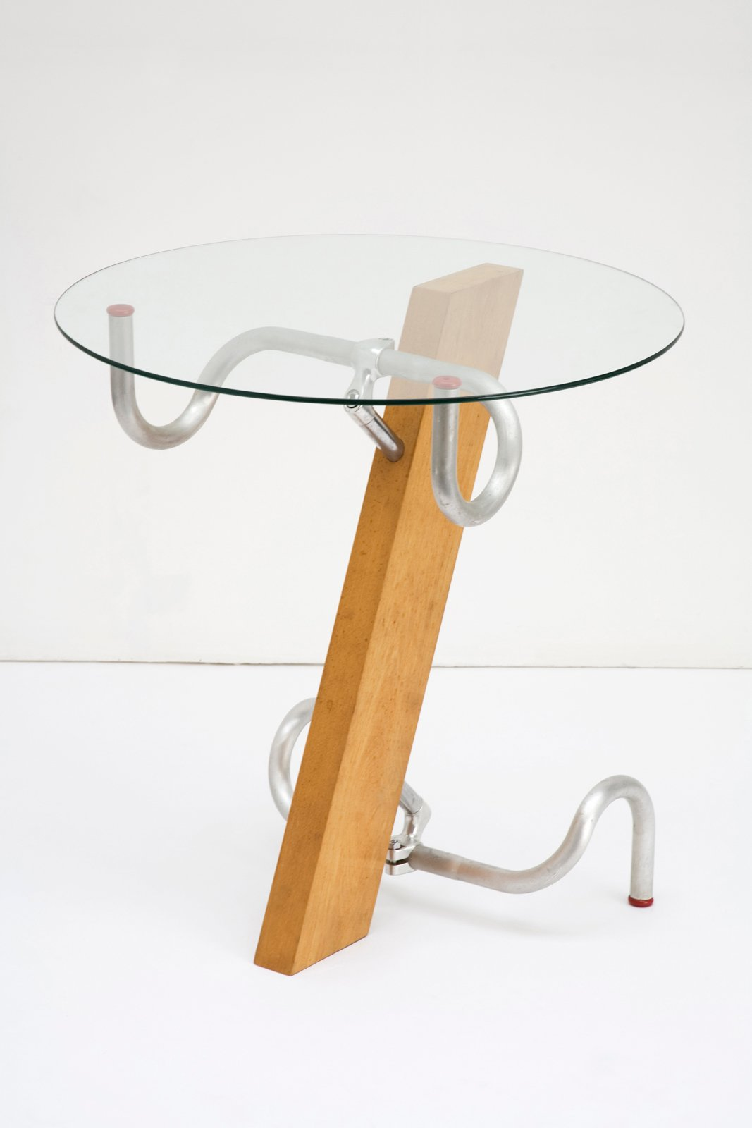 """Early in Jasper Morrison's career, he built a table of beech wood, glass, and two bicycle racing bar handles to give the piece a """"mass-produced quality"""" without benefit of a manufacturer. In 1983, the materials for one table cost about £20.00, and he sold them for five times that. """"The somewhat eclectic shape of the table itself was fitting to the mood of the time and my own frame of mind, a kind of poetic, anti-establishment, business-like attitude,"""" Morrison is reported as saying years later.  Design Museum London's Extraordinary Stories about Ordinary Things by Rebecca L. Weber"""
