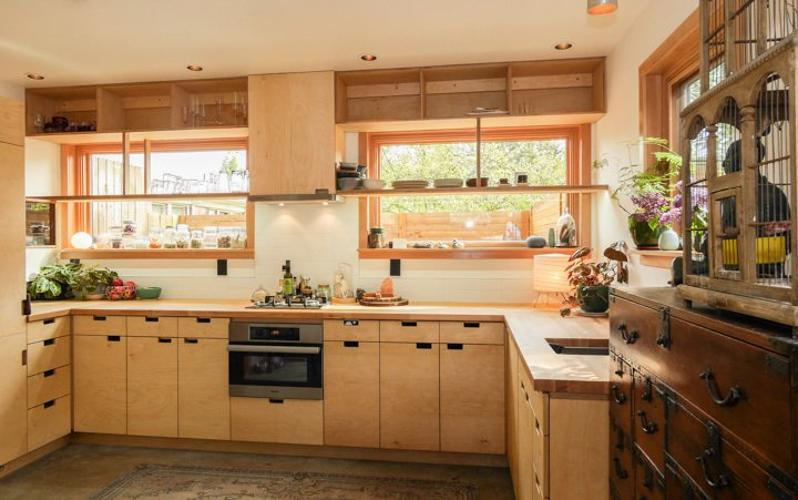 """""""We took a lot of time designing the cabinets,"""" Baird says. """"We wanted the refrigerator to be hidden, to have as many windows as possible with views to the garden and courtyard, and to have no upper cabinets."""" Baltic birch plywood cabinets are paired with white oak countertops. The combination speed oven, microwave, and convection oven is from Miele.  Take Me to Birch: 8 Houses that Make Use of Birch Wood by Luke Hopping from Cozy Home in Portland Is Under 800 Square Feet"""