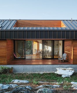 """Rocks that were unearthed while digging the foundation make up the hardscape in the rear, beyond the open porch. """"It's one of my favorite parts of the house,"""" says resident Laura Sohn. Sanders Pace Architecture finished the exterior in western red cedar treated with Sikkens Cetol."""