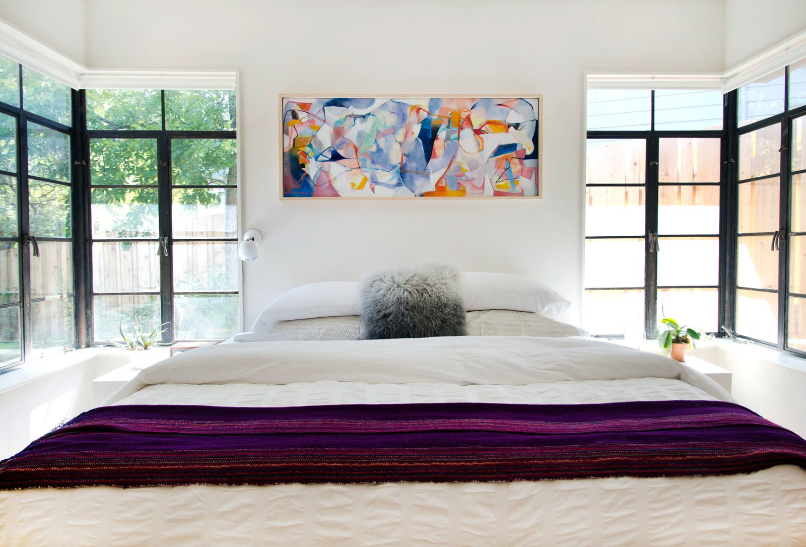 "The bedroom enjoys ample natural light, thanks to the windows on either side of the Charles Rogers bed. ""We centered all our bedroom doors around the central hallway skylight,"" says Allison. The painting is by Pat Diaz.  Bedrooms by Dwell from A Charming Renovation in Austin"