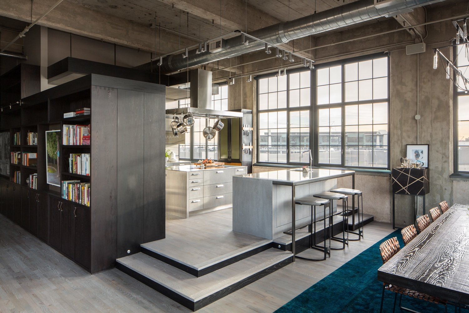 The 1920s building was converted into lofts in 2000. The client started out looking for new cabinet hardware and an improved connection between the laundry room and the guest bath, but ultimately decided to work with the firms on a full overhaul.  Industrial Loft in a Former Flour Mill by Allie Weiss