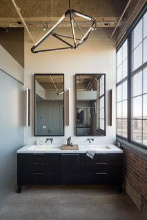A SHY 04 pendant light from Bec Brittain adorns the master bath. The custom vanity is made from oak charred with Shou sugi ban. The fixtures are Grohe.