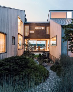 Gray Organschi took down a worn-out 1970s summer home and reinvented it as a serene pair of bleached cedar volumes connected by a glass bridge.