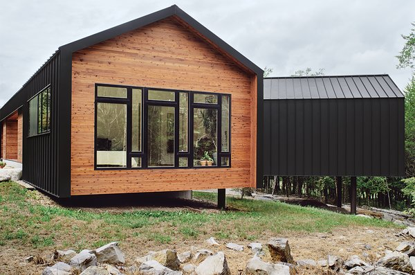 "The metal cladding, inspired by a nearby zinc mine, continues seamlessly onto the house's roof for a minimalist shed effect. ""The drip edge turns to make the wall,"" explains architect Brandon Pace, ""but changes above the window to accommodate a downspout. Any place where the metal contacts glass, or where you walk underneath, we have an internal gutter."""