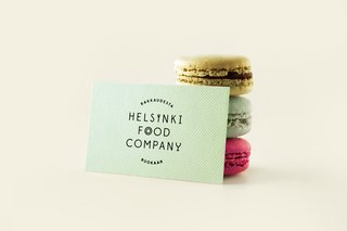 A design and production service provider to the food industry, Helsinki Food Company's pastel colored business card leans against a trio of macaroons.