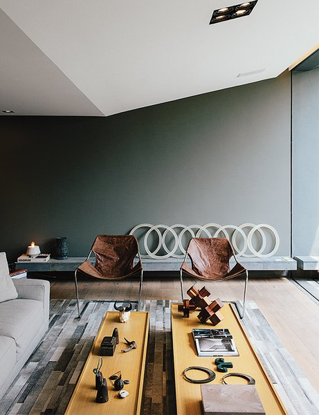In the sitting area, two leather Paulistano chairs by Paulo Mendes da Rocha top a rug by Yerra; the wall paint is Comex.