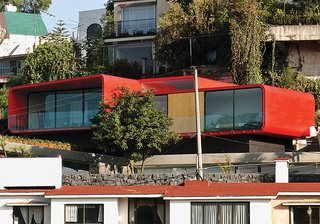 One of Rojkind's first commissions, in 2001, was a rooftop apartment for a ballerina above her father's 1960s-era house in the Mexico City suburb of Tecamachalco. Dissatisfied with the look of the Cor-Ten steel exterior, Rojkind hired auto-body workers to finish it with a coat of red automotive paint.