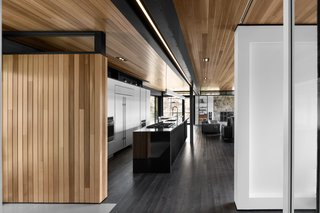 Cedar planks and gray-stained oak flooring line the interior. A minimalist LED lighting strip by Systemalux runs through the kitchen area, enhancing the wood ceiling's reddish tone.