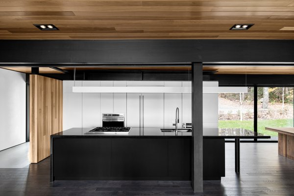 A dramatic black island is expertly balanced by a wall of white cabinetry and a refrigerator that blends perfectly. The kitchen's black countertops were cut from Nero Assoluto granite. The sink and faucet are from Quebec-based company Rubi. Appliances are from Wolf.