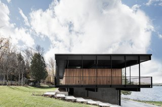"""The original design did not exploit the lower part of the house, so Carle added a bar and lounge area facing the lake at the ground level. He also installed water-based geothermal heating in the basement. """"It allows the concrete floor to be heated and to generate most of the heating of the house, while a second smaller air pump assures a supplement of air on the ground floor and air conditioning for summer."""""""