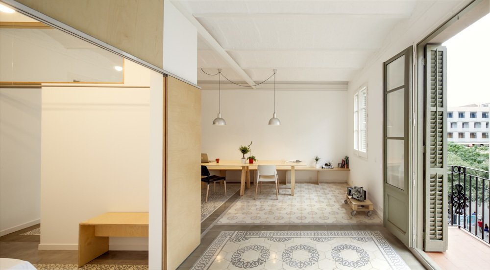 Barcelona-based architect Adrian Elizalde embarked on a renovation project for his family's new apartment. His strategy was to inject some Scandinavian cool on a limited budget, using custom wood pieces and a sparse aesthetic to open things up. Lamps sourced from secondhand stores and a set of Belloch chairs by Santa & Cole are arrayed across the space.  Photo 2 of 8 in 1930s Barcelona Apartment Gets a Minimal Makeover