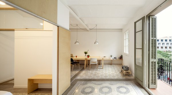 Barcelona-based architect Adrian Elizalde embarked on a renovation project for his family's new apartment. His strategy was to inject some Scandinavian cool on a limited budget, using custom wood pieces and a sparse aesthetic to open things up. Lamps sourced from secondhand stores and a set of Belloch chairs by Santa & Cole are arrayed across the space.