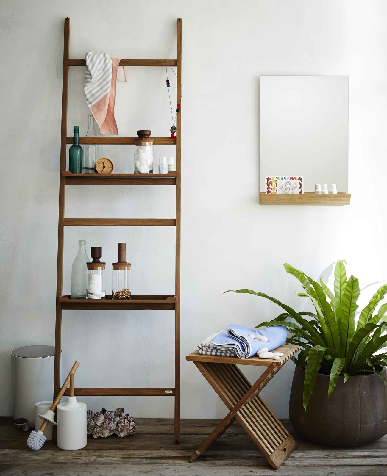 "The Nomad Shelf System from Skagerak is part of an innovative storage system that has a thin, space-saving profile. Designed to resemble a ladder, the Nomad rests on the wall, keeping a small footprint. The ladder comes with four hooks, which make it easy to hang small accessories, and the rungs of the ladder can be draped with towels. The Nomad Ladder can be used with the Nomad shelf to create more surface area for storing other items.  Search ""bathroom storage"" from Modern Ladders"